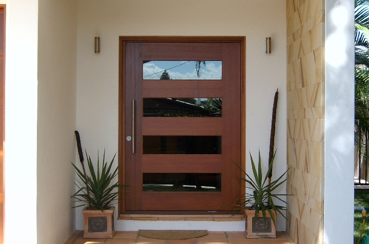 A photo of a large pivot door at the front entrance of a luxury home.