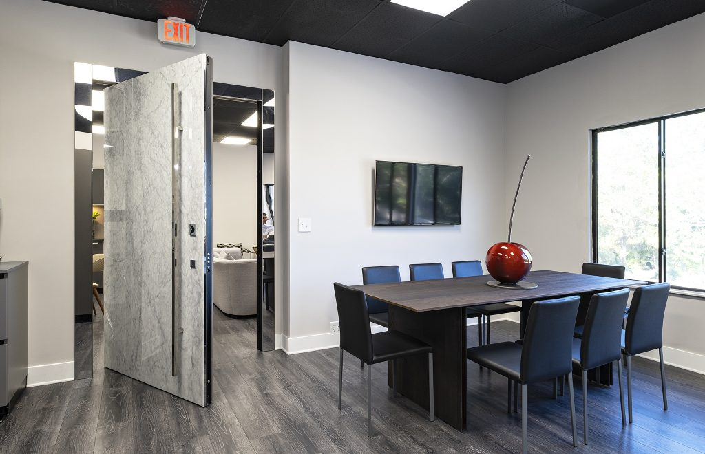 A photo of a large pivot door in an office setting.