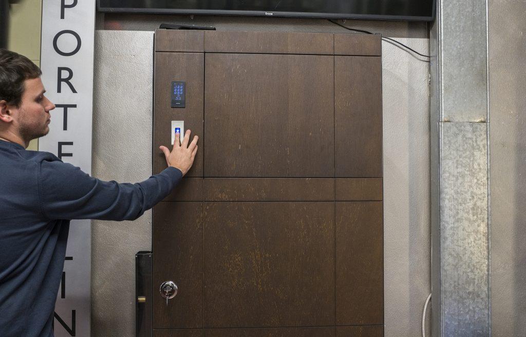 A photo of an Italian artisan testing the fingerprint scan on a custom security door.