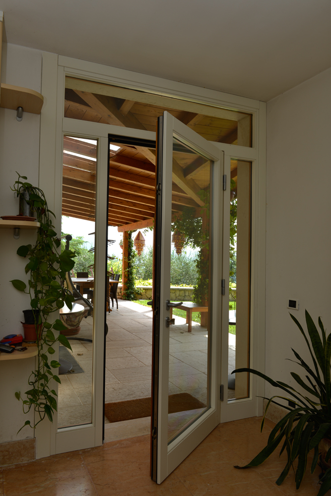 A photo of a glass hurricane certified hinge door opening to a patio.