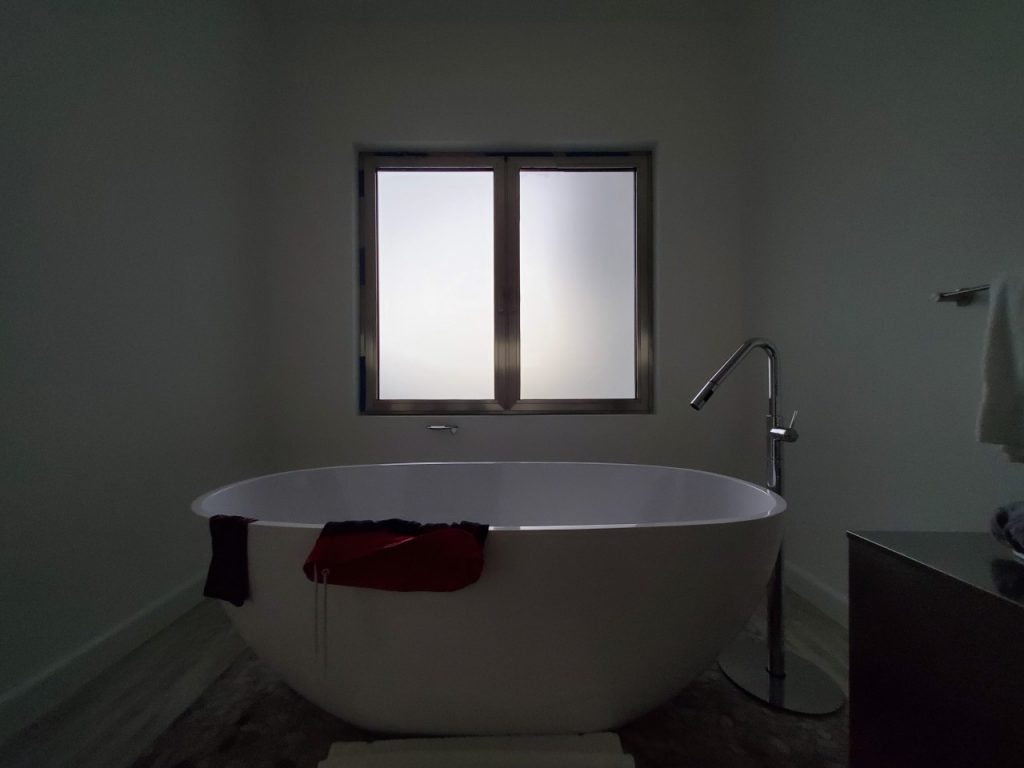 A photo of a large soaker tub in front of a frosted custom security window.