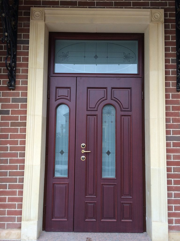 A photo of a luxury front door in a rich mahogany on a brick home.