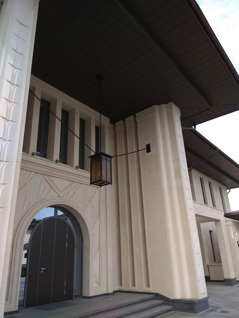 A photo of the grand entrance of a very large luxury home, complete with an arched front door and a chandelier.