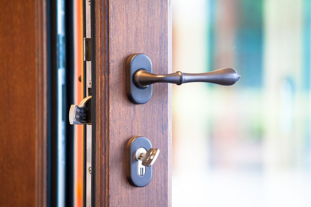 A close-up photo of a glass door with a high security lock installed.