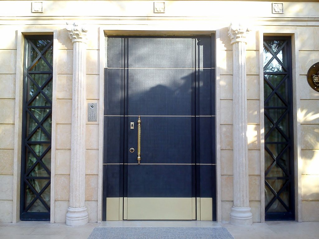 A photo of a steel security door finished with blue panels and gold accents.