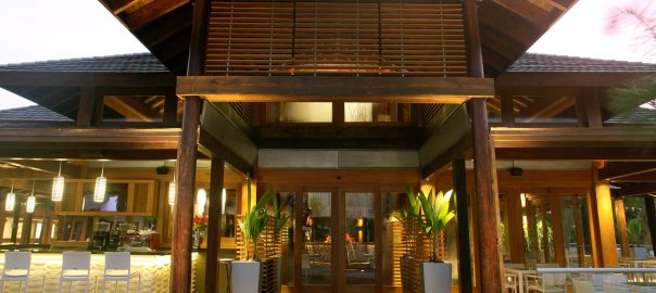 A photo of the front entrance of a high-end restaurant with a luxury front door made of wood and glass.
