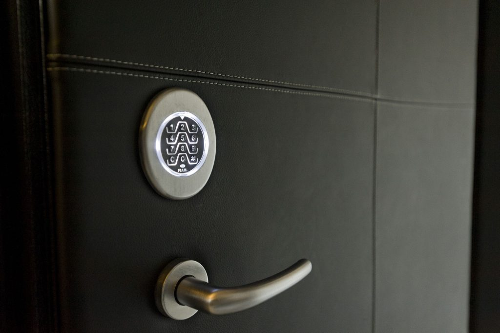 A close-up photo of a steel security door finished in hand-stitched Italian leather featuring a keypad lock.
