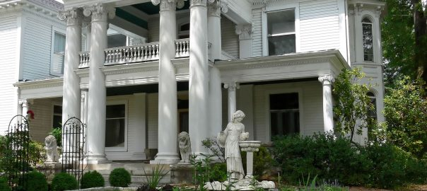 A photo of the exterior of a luxury home with large columns and statues out front.