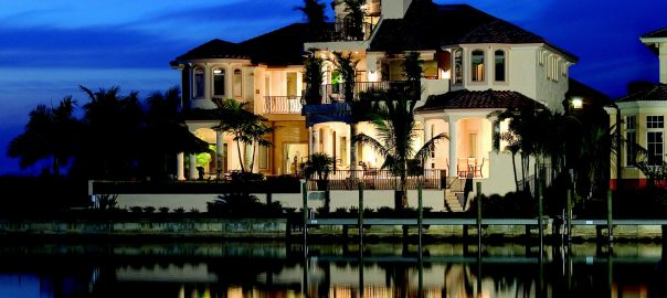 A photo of a waterfront luxury home in Miami lit up brightly at dusk.