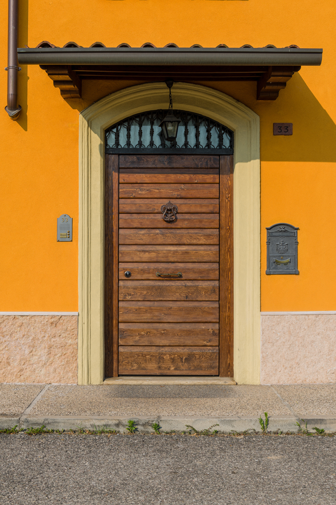 A photo of a steel security door finished with wood and an elegant door knocker.