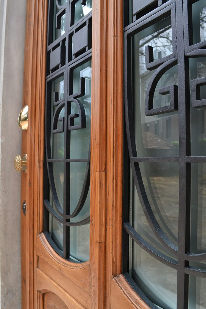 A photo of an elegant steel security front door finished with wood and glass.