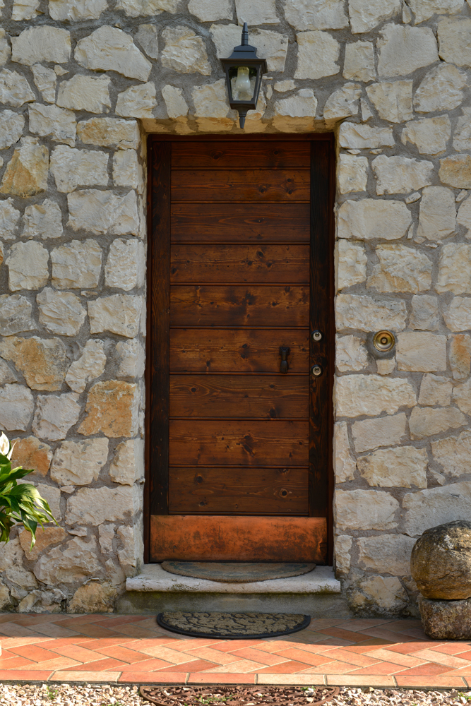 A photo of a steel security door finished with real wood on a stone building.