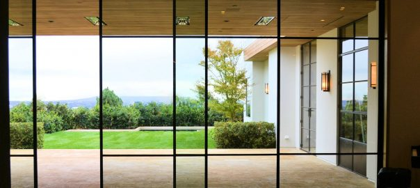 A photo of sliding glass doors that cover an entire wall leading out onto a covered patio.