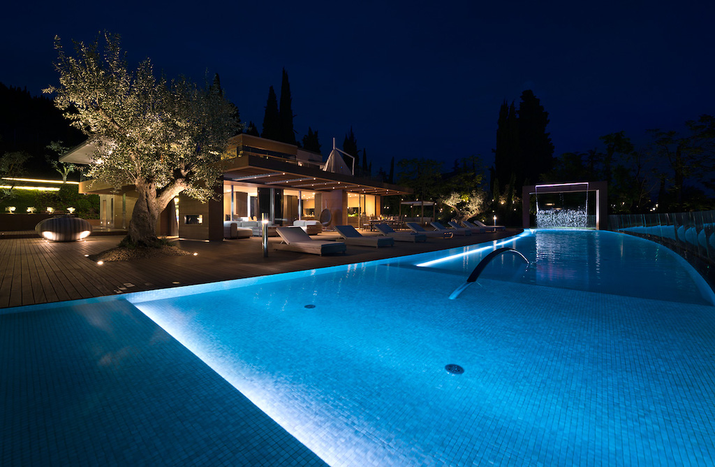 A nighttime photo of the exterior of a brightly lit luxury home with a large pool in the backyard.