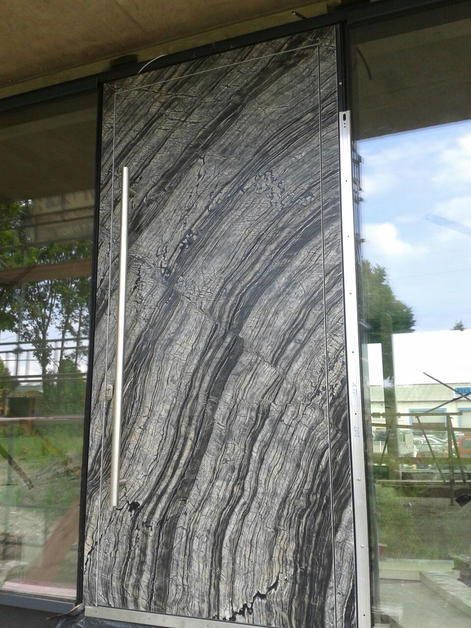A photo of an oversized security door made with a custom marble covering.