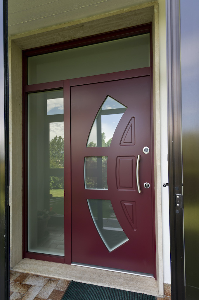 A photo of a security door made of glass and wood at the front entrance of a luxury home.