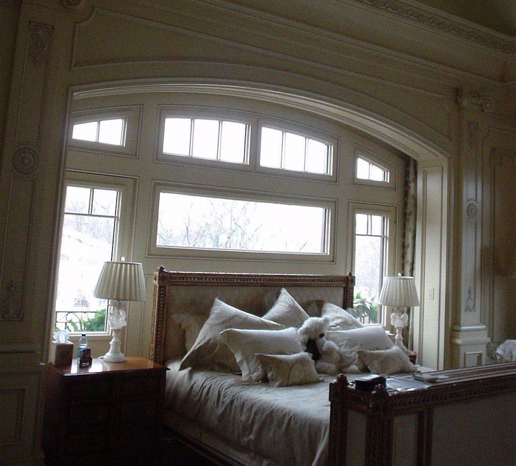 A photo of a bed surrounded by security windows in the master bedroom of a luxury home.