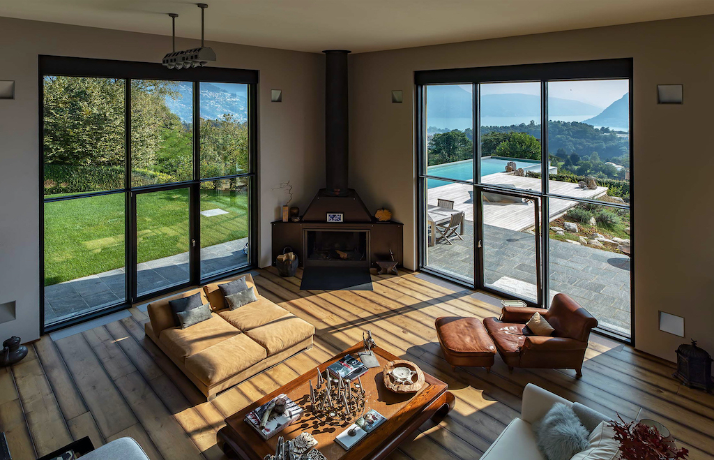 A photo of a living room in a luxury home with floor to ceiling windows overlooking the mountains.