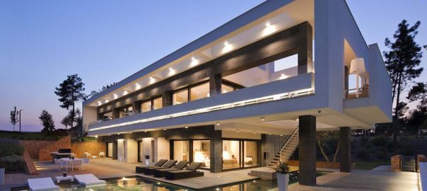 A photo of the exterior of a modern luxury home lit up at dusk.