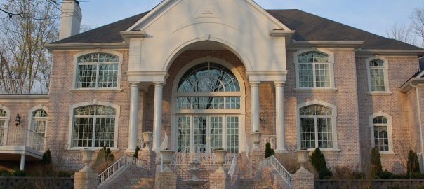 A photo of the exterior of a large brick luxury home with glass double security doors surrounded by custom security windows.