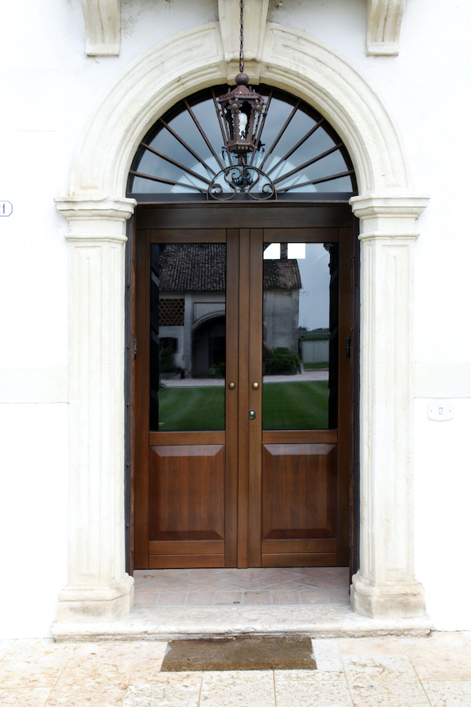 A photo of custom double security doors made of wood and glass at the front entrance of a luxury home.