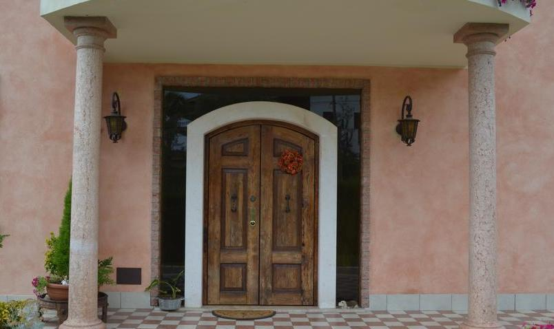 A photo of the front entrance of a luxury home in Italy with solid wood double security doors.