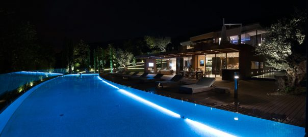 A photo of a luxury home with a large pool lit up at night.
