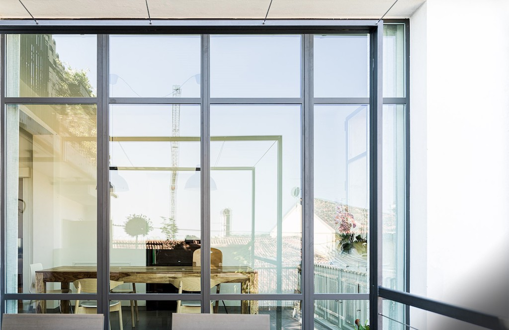 A photo of a wall of windows dividing a modern living space and an outdoor patio.