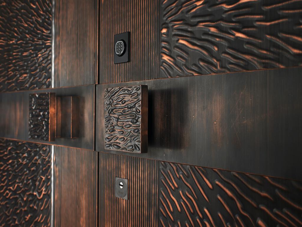 A photo showing a bronze security door with custom luxury door handles.
