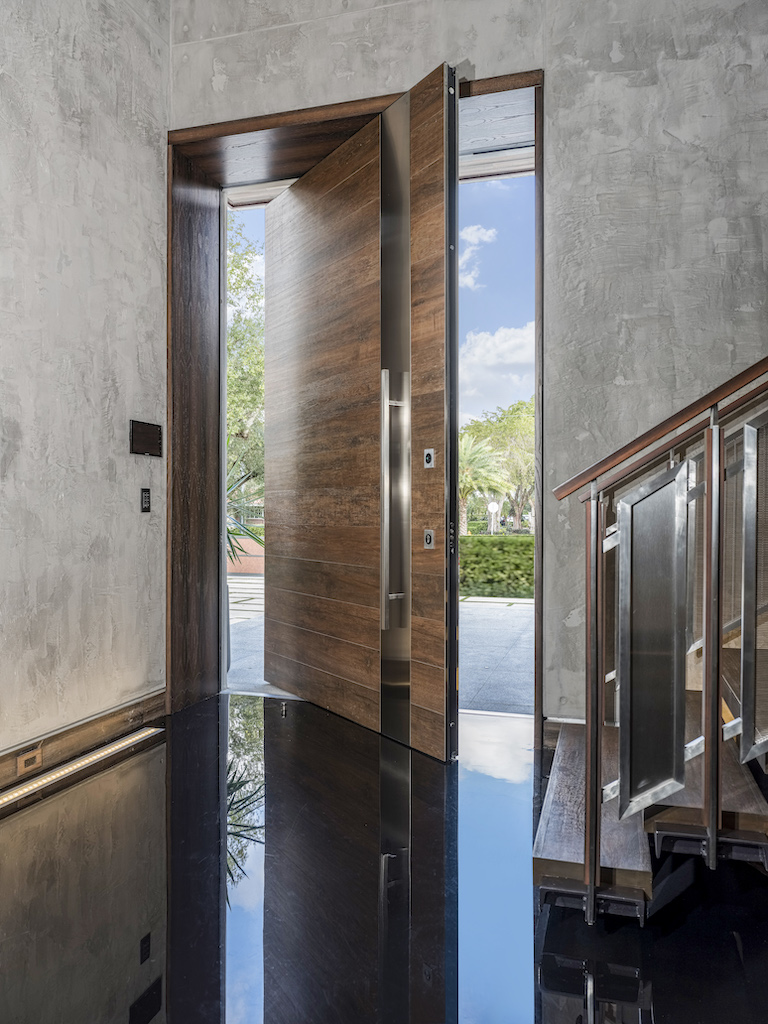 A photo of the interior side of an oversized pivot door from the foyer of a luxury home.
