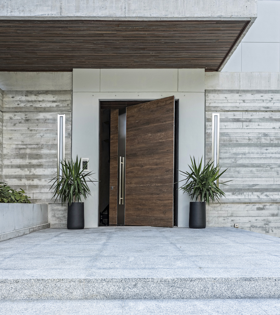 A photo of an oversized pivot door covered in wood and stainless steel at the front entrance of a luxury home.