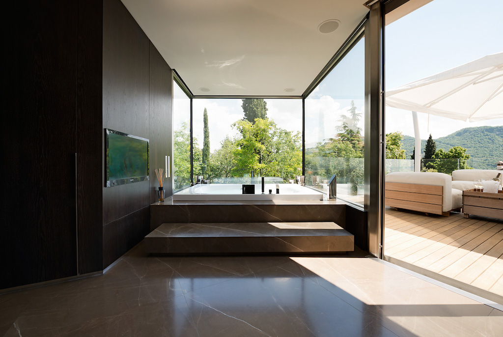 A photo of the master bathroom featuring two walls of security windows in a luxury home, opening to a patio.