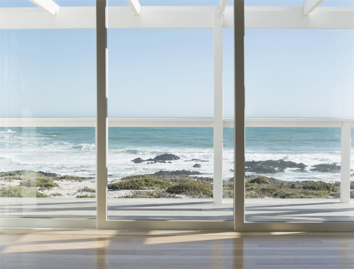 A photo of a sliding glass door made from security glass overlooking an ocean view.
