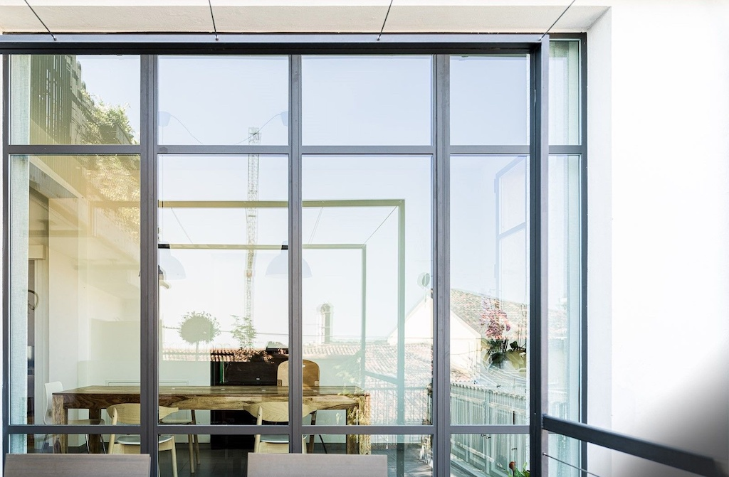 A photo of a window wall made from security glass overlooking an outdoor seating area on a patio.