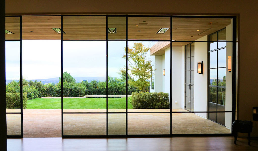 A photo of a security glass window wall opening up to the private backyard of a luxury home.
