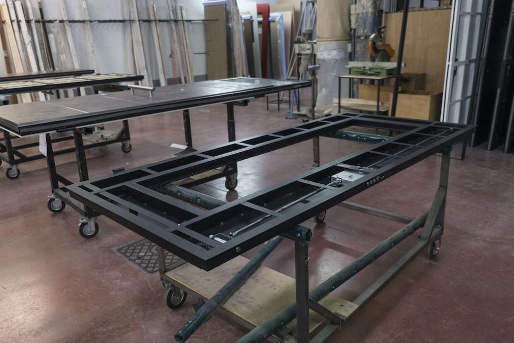 A photo of custom security doors in various states of production, including the plain steel frame and another nearly finished.