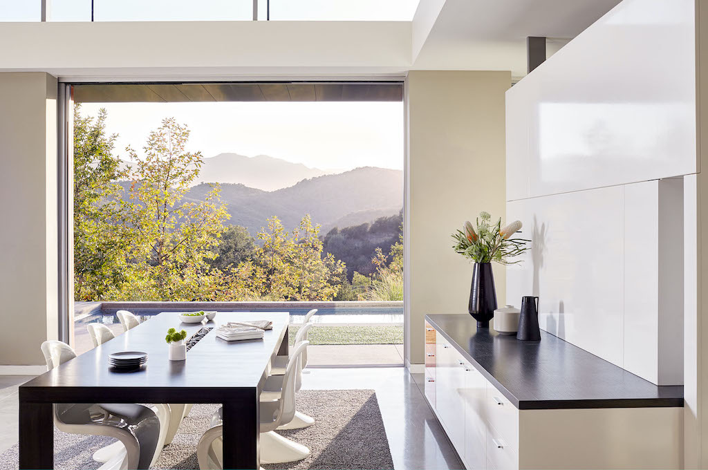 A photo of a luxury home dining room with a large fixed window overlooking mountains.
