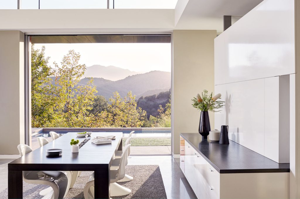 A photo of a bright dining room in a luxury home with a view of the mountains.