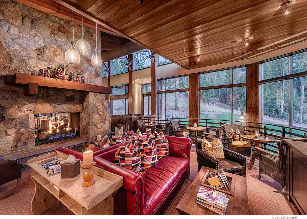 A photo of a rustic luxury home living room featuring large fixed windows.