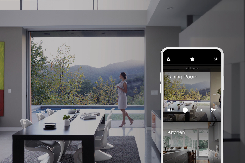 A photo of a woman walking through her dining room in front of a massive window wall displaying the mountains behind her.