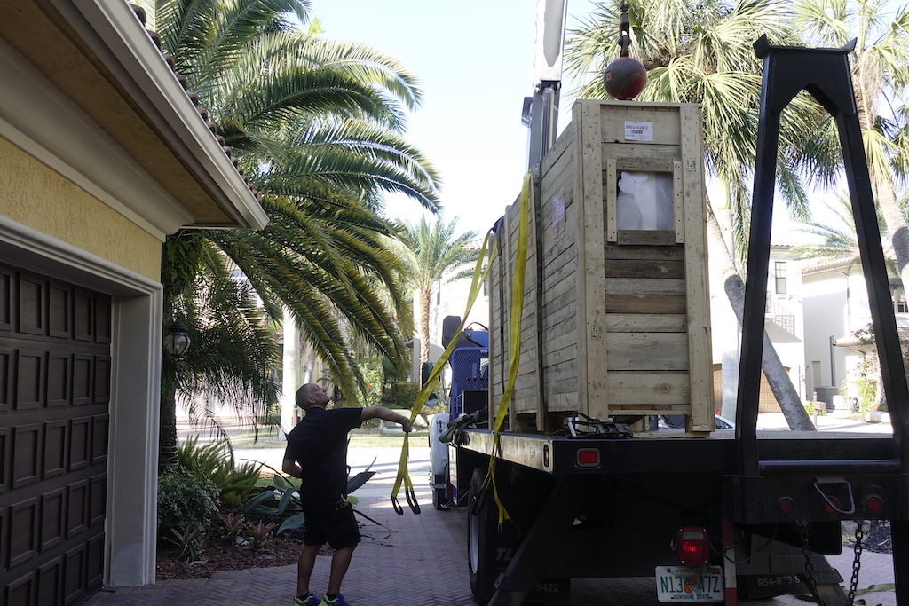 A photo of a crane-truck delivering a custom security door to a luxury home.