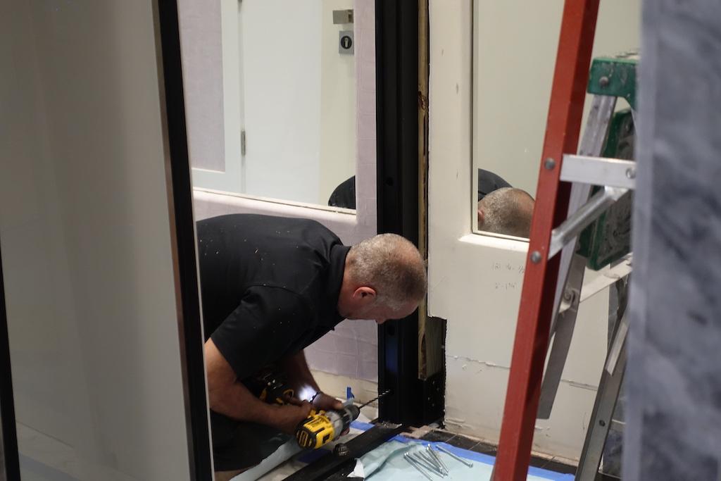 A photo of a contractor installing a custom security door.
