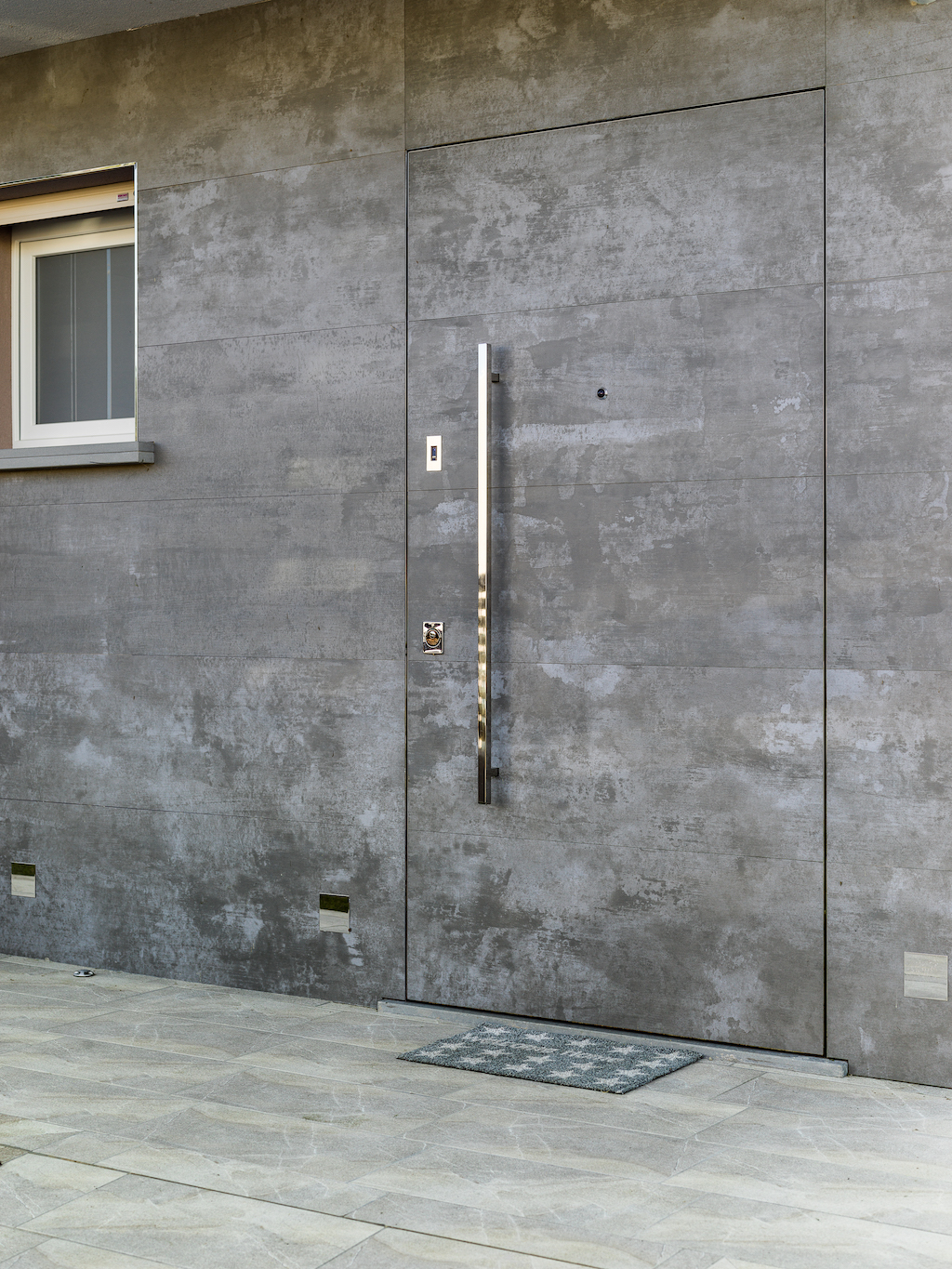 A photo of a front entry frameless door designed to match the exterior wall seamlessly.