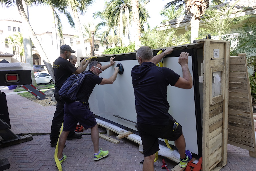 A photo of a team of movers unpacking a custom security door outside a luxury home.