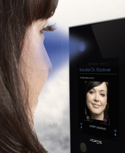A photo of a woman standing in front of an Adatis facial recognition panel as it scans her face.