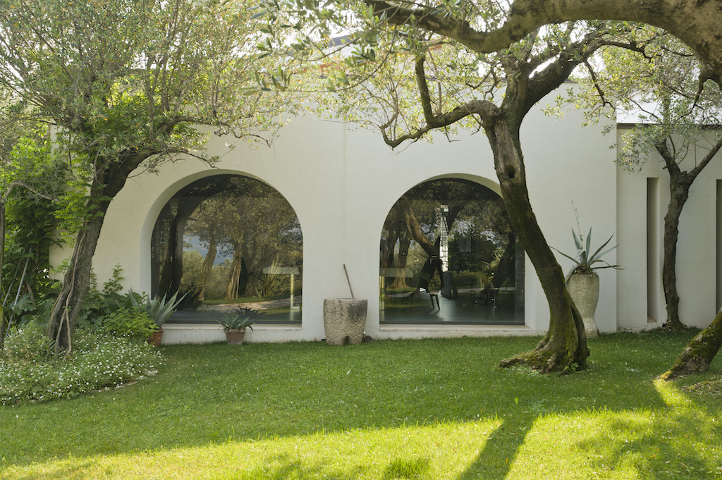 A photo of the courtyard behind a luxury home featuring two large, arched security windows.