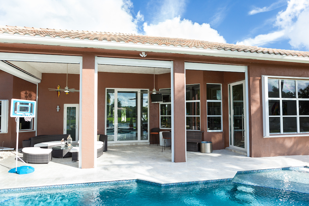 A photo of the back of a luxury home, complete with a beautiful patio, a pool, and large security windows.
